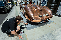 """© Licensed to London News Pictures. 01/06/2021. LONDON, UK. Installers put the finishing touches to """"Ferrari 250 GTO"""", 2021, by Anthony James, a copper chassis in New Bond Street, one of 22 public outdoor sculptures installed as part of this year's Mayfair Sculpture Trail and can be seen around Mayfair 2 to 27 June.  The sculpture trail forms part of the eighth, annual edition of Mayfair Art Weekend which celebrates the rich cultural heritage of Mayfair as one of the most internationally known, thriving art hubs in the world with free exhibitions, tours, talks and site-specific installations available to the public.  Photo credit: Stephen Chung/LNP"""