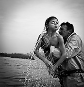 """A child comes out of the water during a """"holy bath"""" on the St. Bartolomeu celebration. The """"holy bath"""" is believed to drive away evil and cure diseases related with """"demonic possession"""", such as stuttering or epilepsy. This tradition that dates back to the sixteenth century (1566), and it claims the devil is on the loose during this day. Every year on 24 August  faith and tradition join thousands of people at the feast of St. Bartolomeu do Mar, for ritual that mixes the sacred and the profane."""