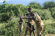 Hadza (Hadzabe) man aiming an arrow at a bird during a hunting expedition. Hatzabe are a Small tribe of hunters gatherers in east Africa. Photographed at Lake Eyasi, Tanzania