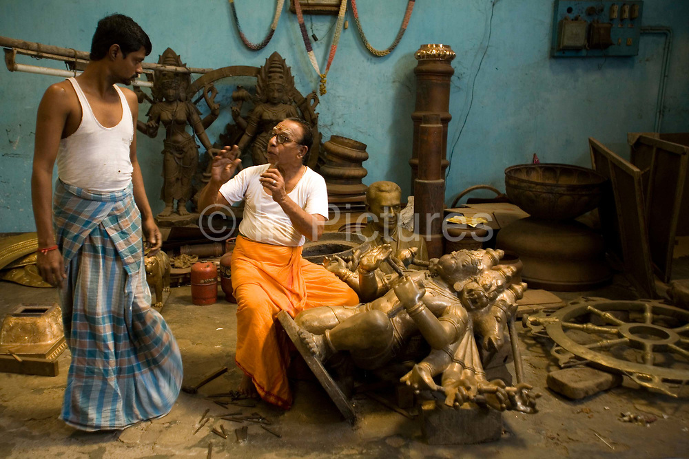 Master craftsman Pranava Stapathy instructs another craftsman whilst working on a large statue of Hanuman, the monkey God at the workshop of S. Devasenapathy Stapathy and Sons..The current Stpathy family is the twenty third generation of bronze casters dating back to the founding of the Chola Empire. The Stapathys had been sculptors of stone idols at the time of Rajaraja 1 (AD985-1014) but were called to Tanjore to learn bronze casting. Their methods using the ,ƒÚlost wax,ƒÙ process remains unchanged to this day.