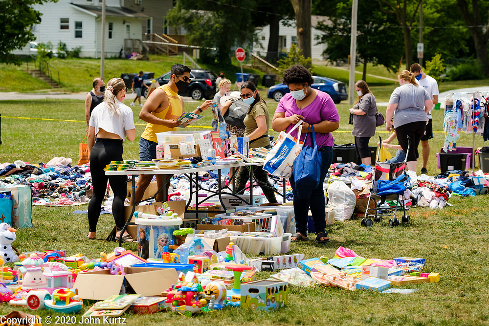 """19 JULY 2020 - DES MOINES, IOWA: A woman looks at books during """"A Celebration of Black Motherhood"""" in Des Moines Sunday. The event was organized by the Supply Hive and Black Lives Matter. Items were donated by members of the community and redistributed to at risk families. They distributed diapers, sanitary products, clothes, books, and toys. They had enough material to help 200 families.PHOTO BY JACK KURTZ"""