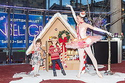 Scottish Ballet dancer Grace Paulley joins local children in front of a festive gingerbread house ahead of the opening night of Hansel and Gretel.<br /> <br /> Pictured: Niamh Kelly (aged 3) and Teddy Miller (aged 4) with Grace Paulley