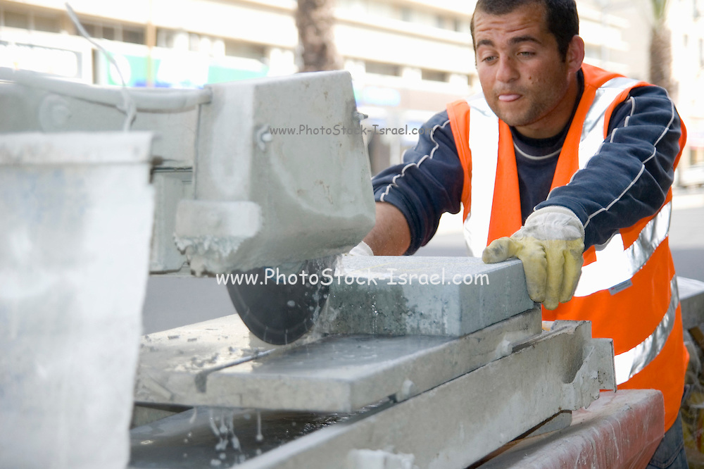 Israel Tel Aviv, Road works and infrastructure replacement in Ibn Gvirol street worker cutting paving stones to size