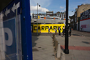 Pedestrians walk past large yellow car park sign on street in East London.