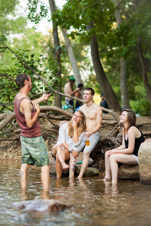 Friends chat out on the banks of Boulder Creek at Eben G. Fine Park on a hot summer day in Boulder, Colorado.