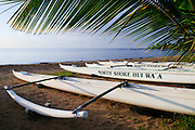 Outrigger canoes sit in the sand at Hale'iwa Beach Park on the North Shore of Oahu, Hawaii.