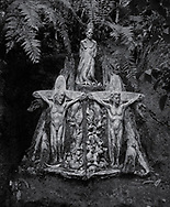 William Rickets Sanctuary - Black and white photo art print of Sculpture of Aboriginal and white man on a crucifix in the deep woodland of the Dandenon Mountain near Melbourne Australia. Taken 1993 by Paul Williams,