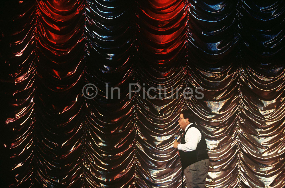 A comic entertainer with glitzy backdrop performs a stand-up routine on stage during cruise ship voyage. Surrounded by the showbiz styled curtain (drapes) we see the rather fat man wearing a waistcoat and bow tie as he paces around the stage while entertaining the ship's evening audience. The MS Ecstasy is a Fantasy class cruise ship with whirlpools, nightclubs, a casino and duty-free shopping. Carnival's ships are known for their Las Vegas decor and entertainment, calling its vessels Fun Ships.