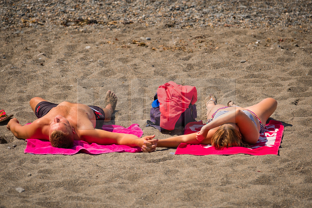 ©Licenced to London News Pictures<br /> 07 July 2018, Aberystwyth, UK.A couple holding hands and relaxing on the beach  in Aberystwyth on yet another scorchingly hot and cloudless day, as the prolonged heatwave continues to dominate the weather over the UK. Photo creditKeith Morris/LNP