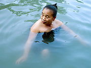 A Lao woman washing and relaxing in Nameuang hot springs after working in the fields, Houaphan province, Lao PDR.
