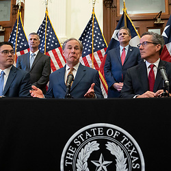 Texas Gov. Greg Abbott talks to the press after signing two bills strengthening the Texas power grid and infrastructure that were emergency items on his legislative agenda. The bills were in response to February's winter storm that nearly knocked out the Texas power grid.  At left is Rep. Chris Paddie, R-Marshall, at right, Sen. Kelly Hancock, R-North Richland Hills.