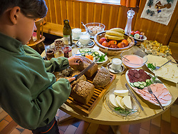 Girl having breakfast in a mountain hut Naturfreundehaus Feldberg, Feldberg, Baden-Württemberg, Germany