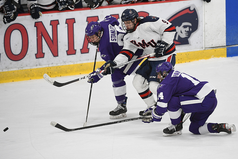 PITTSBURGH, PA - MARCH 12: Jordan Timmons #9 of the Robert Morris Colonials battles for a loose puck with Brandon Stanley #26 of the Niagara Purple Eagles in the third period during Game One of the Atlantic Hockey Quarterfinal series at Clearview Arena on March 12, 2021 in Pittsburgh, Pennsylvania. (Photo by Justin Berl/Robert Morris Athletics)