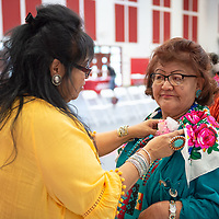 Felda Yazzie, an elder from Tse'ii'ahi (Standing Rock) has a flower pinned on her by Bess Seschillie, one of the fashion show coordinators. The event was held in the Wellness Center in Crownpoint on May 07.