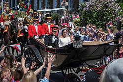 © Licensed to London News Pictures. 19/05/2018. WINDSOR, UK. Prince Harry and Meghan Markle, now The Duke and Duchess of Sussex, ride by in a horse-drawn carriage on a tour of the town after being married in Windsor Castle.  100,000 people wereexpected to visit the town for what has been billed as the wedding of the year. Photo credit: Stephen Chung/LNP