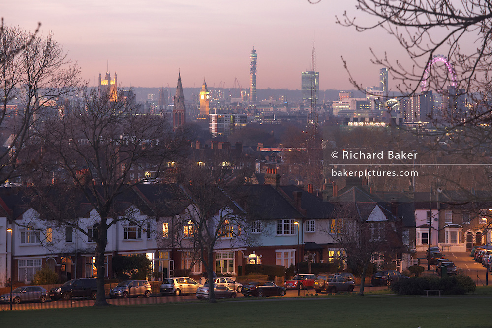 Early evening lights glow from windows of Edwardian era semi-detached houses with 100 year-old mature ash trees and Westminster and city behind, SE24
