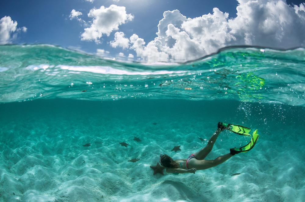 Girl freediving among sea stars in the Bahamas