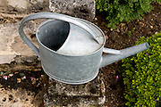 a watering can placed on stairs near flowerbed