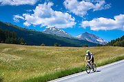 Cycling downhill in the Swiss National Park with background of the Swiss Alps, Switzerland