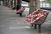 Benches on the South Bank are taped off to prevent people sitting down and so to preserve social distancing as lockdown continues and people observe the stay at home message in the capital on 11th May 2020 in London, England, United Kingdom. Coronavirus or Covid-19 is a new respiratory illness that has not previously been seen in humans. While much or Europe has been placed into lockdown, the UK government has now announced a slight relaxation of the stringent rules as part of their long term strategy, and in particular social distancing.