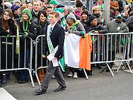 March 16, 2013 - New York, NY, U.S. - A young member of the Line of March Committeo of NYC 2013 St. Patrick's Day Parade, walks along the parade barricades. Tthousands of marchers show their Irish pride, as they march up Fifth Avenue, and over a million people, often in green and orange, watch and celebrate.
