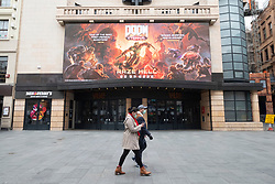 © Licensed to London News Pictures. 17/03/2020. London, UK. Visitors wearing masks walk past a closed Leicester Square cinema due to the Coronavirus outbreak. Photo credit: Ray Tang/LNP