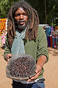 Africa, Ethiopia, Omo region, Chencha, Dorze village. Portrait of young man in modern clothes with coffee beans