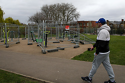 © Licensed to London News Pictures. 28/03/2021. London, UK.  A man walks past the outdoor gym in Chestnuts Park in north London which is vandalised. The next phase of easing of lockdown restrictions on Monday 29 March, will see outdoor exercise being allowed. Photo credit: Dinendra Haria/LNP