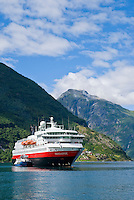 Hurtigruten passanger ferry surrounded by the mountains of Geiranger Fjord, Norway