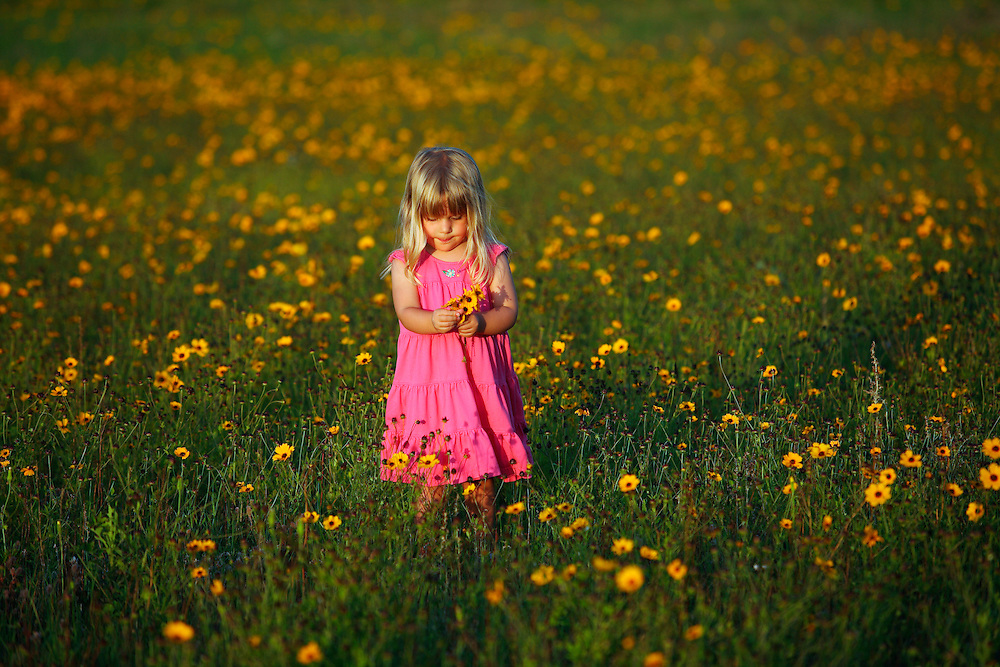 Wilmington, NC - MAY 27: M. Rose picks flowers in a field outside Scott's Hill, near Wilmington, NC. (Photo by Logan Mock-Bunting)