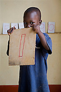 A young boy holds up a sign of his favourite number 1 during a class at Miles2Smiles Welfare Centre in Kalerwe market, Kampala, Uganda. The centre is a day care and welfare service for market vendors with babies and infants aged 6 months to 5 years old.
