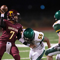 DeAngelo Hunch, quarterback for Tohatchi Cougars looks to throw a pass before being tackled by Luscilliano Delgarito of the Thoreau Hawks Friday Oct. 5, 2018 in Tohachi.