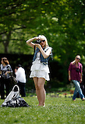A young blond woman takes photos at the the Brooklyn Botanical Garden in New York