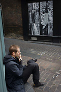 A lone man smokes a cigarette opposite contemporary poster of young people, in London's Carnaby Street. As youths of today are seen in the window of a fashion store on this stylish street in the capital's Soho district. The man draws on his cigarette and inhales while siting on a corner step. He is in deep thought while enjoying a brief respite from a working day.