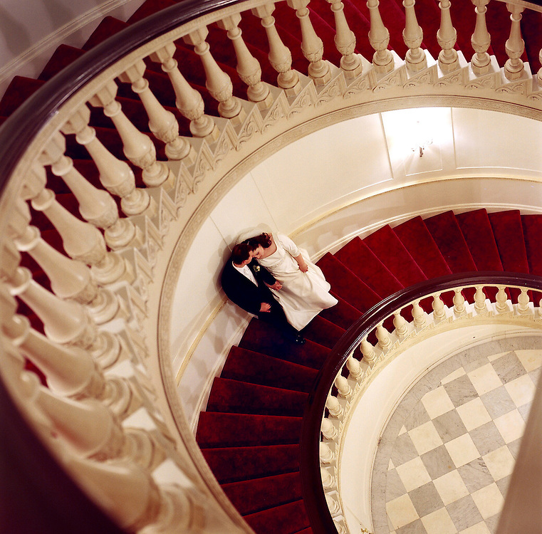 Dramatic Camera angle photo looking down a sweeping circular staircase at bride and groom two floors below