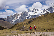 Trekkers walk in Yanayana Valley below Siula Grande. Day 2 of 9 days trekking around the Cordillera Huayhuash in the Andes Mountains, Peru, South America.