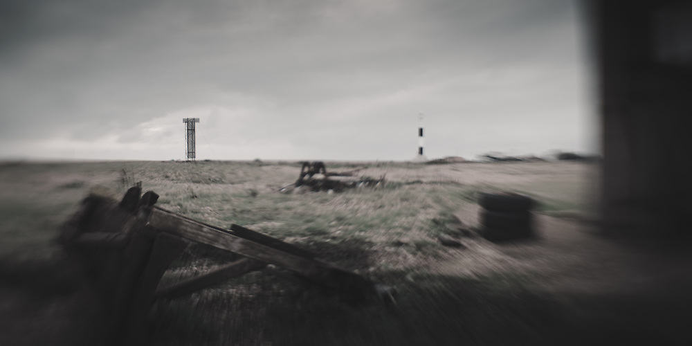 Derelict building, rusting machinery, shipping marker and lighthouse, Dungeness, UK