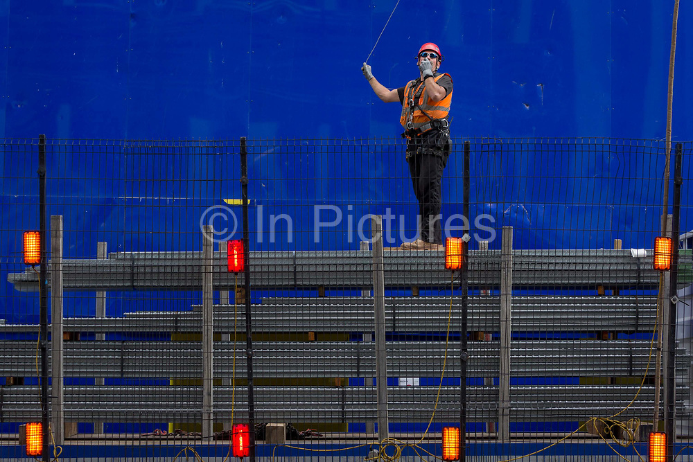 A construction worker supervises the lifting by crane of new flooring to an upper floor at the new development high-rise development at 22 Bishopsgate in the City of London - the capitals financial district, on 21st August 2018, in London, England. 22 Bishopsgate is a commercial skyscraper under construction in London, United Kingdom. It will occupy a prominent site on Bishopsgate, in the City of London financial district, and is set to stand 278 m tall with 62 storeys. The project replaces an earlier plan for a 288 m tower named The Pinnacle, on which construction was started in 2008 but suspended in 2012 following the Great Recession.