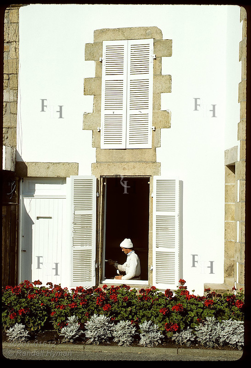 Man painting window sill of white stone house in town of Carnac in Brittany. France