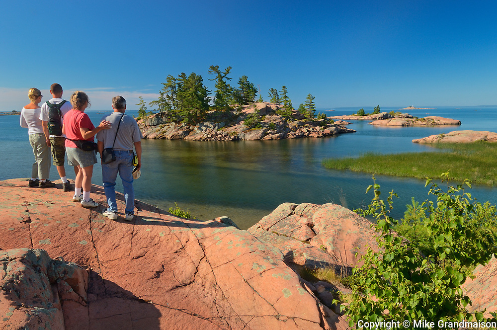 tourists look onwaards from Chikanishing River as it joins Collins Inlet at Georgian Bay. Killarney Provincial Park. Ontario. Canada<br />Killarney Provincial Park.<br />Ontario<br />Canada