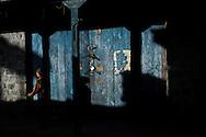 A boy walks down a street as morning light cast it's shadows, Kargil