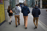 Group of friends all wearing beige or light brown trousers. London, UK.