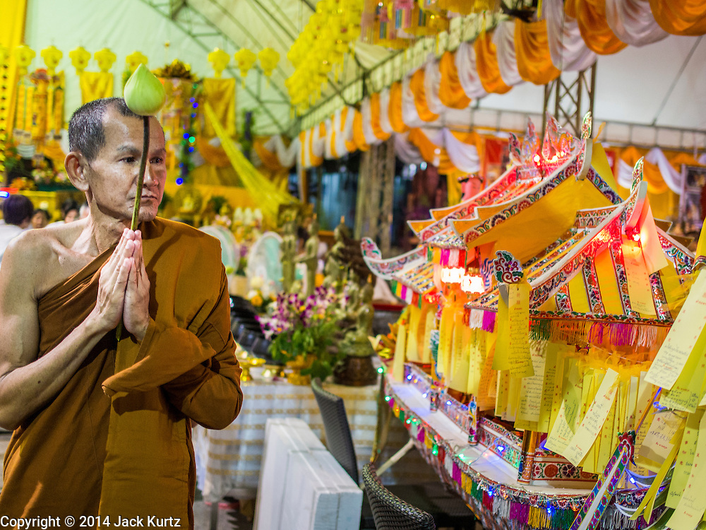 01 OCTOBER 2014 - BANGKOK, THAILAND:  A monk leads a procession before the firewalking at Wat Yannawa (also spelled Yan Nawa) during the Vegetarian Festival in Bangkok. The Vegetarian Festival is celebrated throughout Thailand. It is the Thai version of the The Nine Emperor Gods Festival, a nine-day Taoist celebration beginning on the eve of 9th lunar month of the Chinese calendar. During a period of nine days, those who are participating in the festival dress all in white and abstain from eating meat, poultry, seafood, and dairy products. Vendors and proprietors of restaurants indicate that vegetarian food is for sale by putting a yellow flag out with Thai characters for meatless written on it in red.    PHOTO BY JACK KURTZ