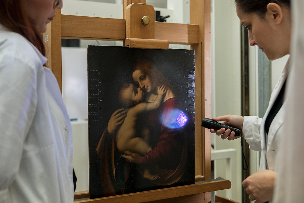 """Milan, Italy, 11 June 2019. The Transparent Restoration laboratory, inside the Pinacoteca di Brera. Paola Borghese, Sofia Incarbone and Ilaria Negri, who together with Andrea Carini constitute the restoration team of the Pinacoteca, are engaged in the observation operation of the painting Madonna with Child by Marco D'Oggiono (painted around 1520). Sofia explains: """"Before proceeding with the restoration of a painting, it is necessary to perform a series of cognitive investigations. In this case we performed multispectral imaging with photographic and reflectographic techniques (in visible light, visible grazing, infrared and ultraviolet, ) that allow us to gain some information about the production technique and the conservation history of the work, which will be  integrated with the historical information that we already know. At this point we did some cleaning tests to find a suitable method to thin out the present paint surface - not original one, which is now yellowed and opaque. The cleaning operation serves to attenuate the visual disturbance created by the yellowed paint and enables us to restore as much as possible the correct chromatic relationships in respect of the original material, taking into account the conservation history of the work and its state of preservation """".<br /> Milano, Italia, 11 giugno 2019. Il laboratorio Restauro Trasparente, all'interno della Pinacoteca di Brera. Paola Borghese, Sofia Incarbone e Ilaria Negri, che insieme ad Andrea Carini costituiscono il team di restauro della Pinacoteca, sono impegnate nell'operazione di osservazione del dipinto Madonna con Bambino di Marco d'Oggiono (1520 ca.) Sofia racconta: """"Prima di procedere con il restauro di un dipinto è necessario eseguire una serie di indagini conoscitive. In questo caso abbiamo effettuato l'imaging multispettrale con tecniche fotografiche e riflettografiche(in luce visibile, visibile radente, infrarossoe ultravioletto) che permettono di avere alcune informazi"""