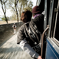 A busboy leans out to call for fares and on the bus to Chitwan, Nepal.