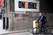 Cycling past the On Your Bike sign on Stainer Street, London. Riding a cycle in London has become more and more popular in recent years. It's a transport revolution that began around the time of the July 2007 attacks as people decided to stay off public transport. Since then the economy has meant that people choose to also save money.