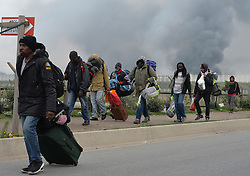 Residents of the Calais Jungle camp on the move as several large fires broke out in the near deserted migrant camp in northern France on the third day of the operation to clear it.