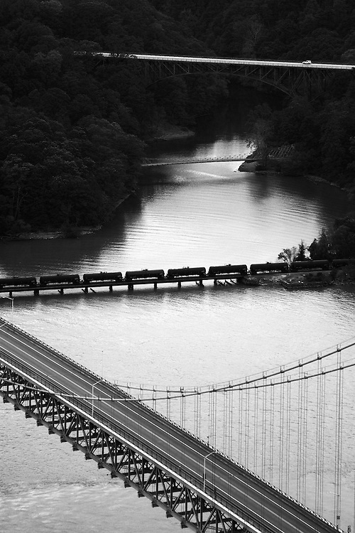 Four bridges are seen from this vantage, but together only carry only a train and a lone vehicle. Closest is the Bear Mountain Bridge, a railroad trestle, a pedestrian bridge that carries the Appalachian Trail, and a vehicular bridge.