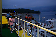 Woman and two children watch as ferry is loaded in pre-dawn light, Island of Korcula, Croatia
