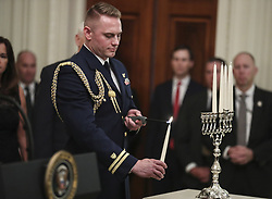 A military aid holds the candle before lighting the menorah during a Hanukkah reception hosted by President Donald Trump in the East Room of the White House on December 6, 2018 in Washington, DC. (Photo by Oliver Contreras/SIPA USA)